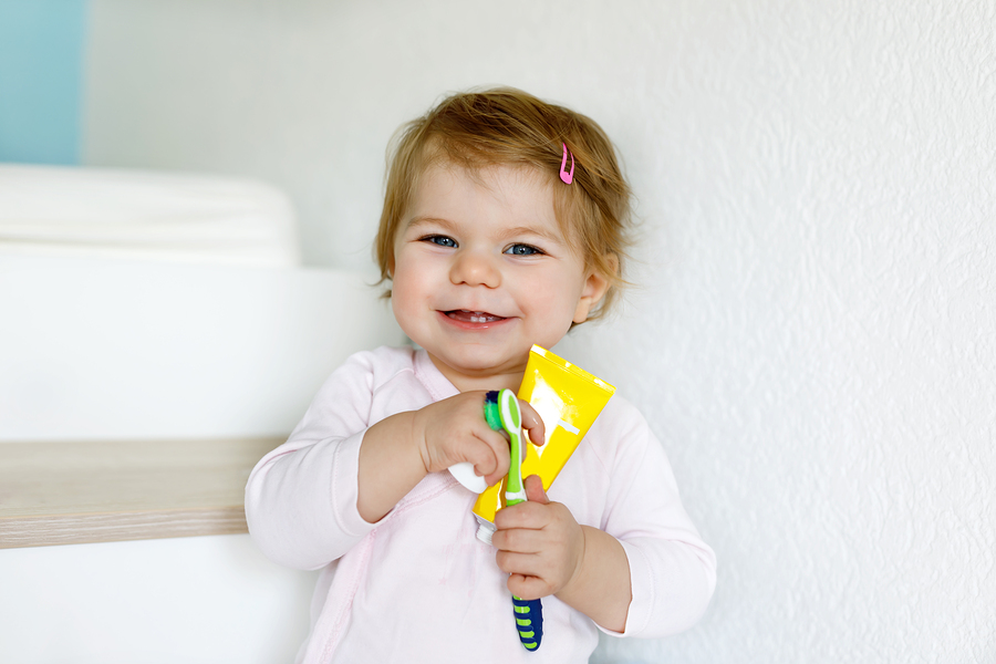 bigstock Little Baby Girl Holding Tooth 228583885
